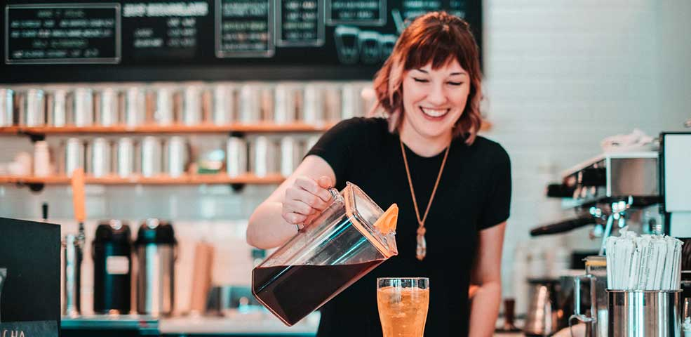 Barista pouring organic iced tea drinks at Amavida Coffee Roasters cafe location in The Market Shops.
