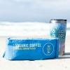 Bag of 30A Florida Sunrise Blend Organic Coffee and reusable travel mug on the beach.