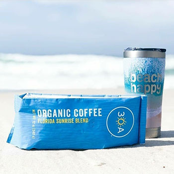 Bag of 30A Florida Sunrise Blend Organic Coffee and reusable travel mug on the beach.